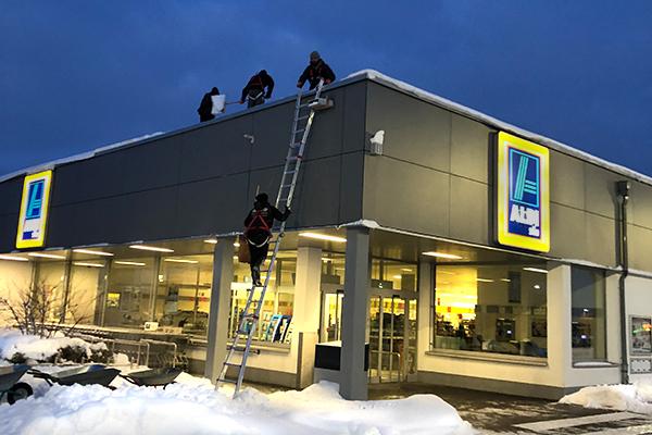 Mitarbeiter befreien ein Dach von Schnee.
